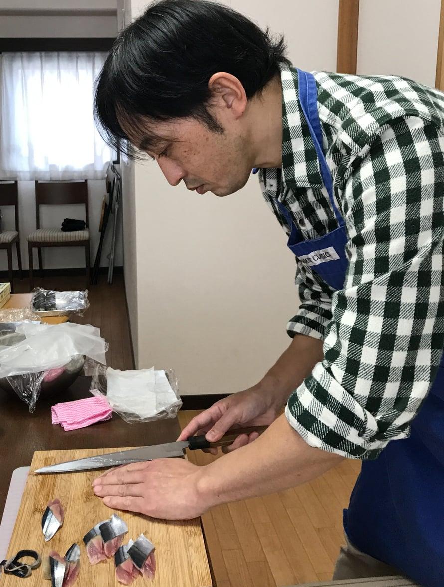 Sushimestari näyttää, miten iso veistä pidetään varmoin ottein. Ja miten sillä leikataan kalaa.