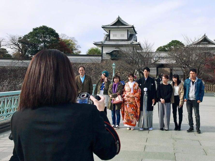 Häävieraat ja morsiuspari Kanazawan linnan portilla.