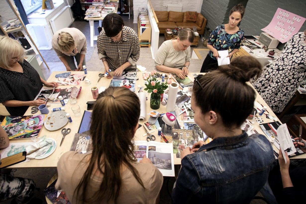 Ensin pöydän ääressä pulistaan, sitten keskitytään. Collage Clubin työpajassa Riitta Skytt (vas.), Jenni Ylinen, Loi Oleinik ja Leena Holmila leikkaavat, sommittelevat ja liimaavat.