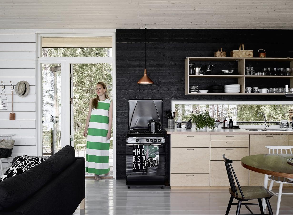 Keittiön taustaseinä on käsitelty mustaksi. Lotta Harald suunnitteli kaapistojen ovet, ja puuseppä toteutti ne vanerista.