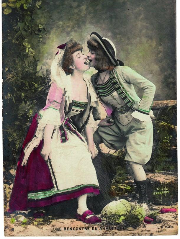 """Vanhoissa postikorteissa kaikki ei ole aivan sitä miltä näyttää. Ranskassa suosittuja olivat sata vuotta sitten kortit, joissa sotkettiin sukupuolirooleja. Romanttisen pariskunnan miespuolisko paljastuikin naiseksi. """"Kohtaaminen Bretagnessa"""" postitettiin Ranskassa vuonna 1905."""