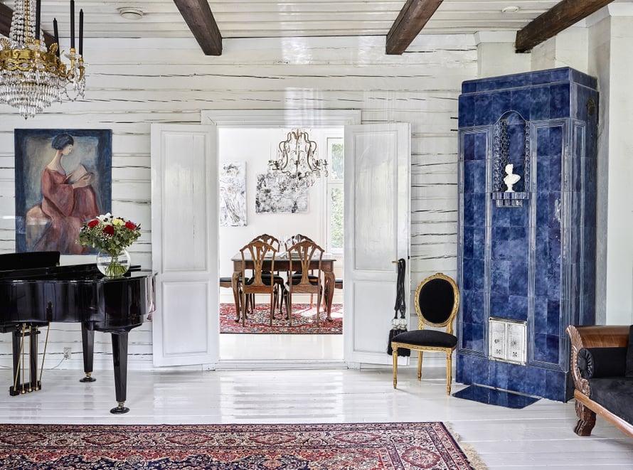 Valkoiset seinähirret saavat salin sinisen kakluunin loistamaan. Antiikkituolin Pekka huusi nettihuutokaupasta ja verhoili mustaksi.
