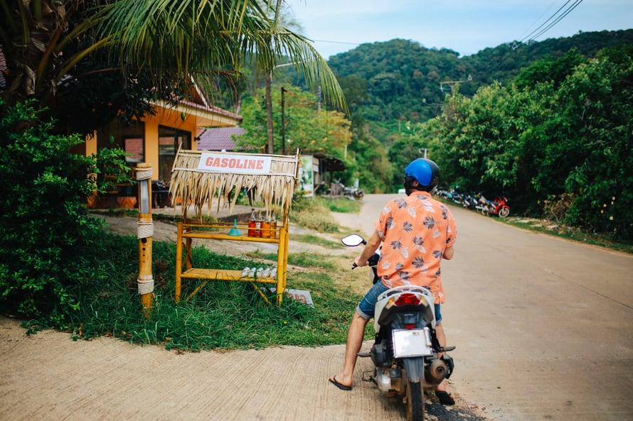 Pienet matkat taittuvat Koh Lantalla mopolla. Polttoainetta myydään pulloissa tien varrella.
