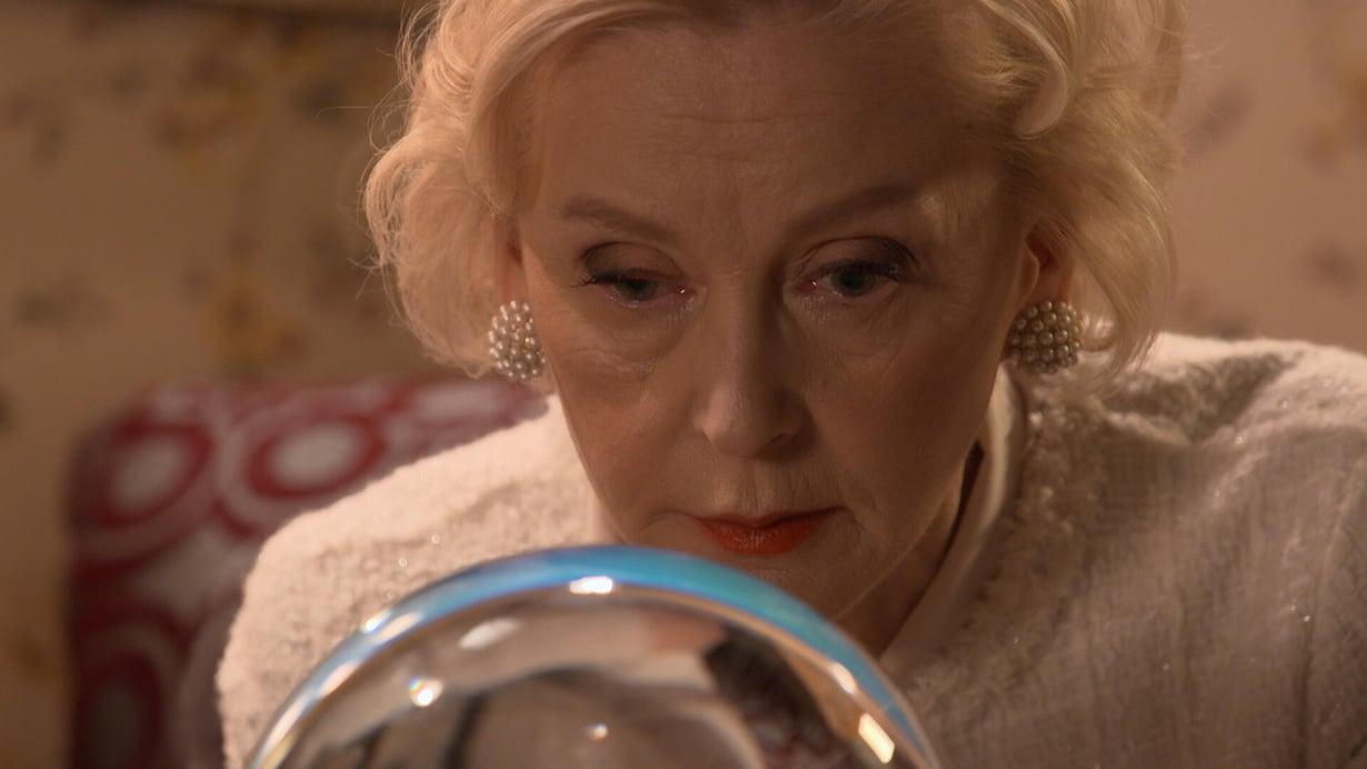 Dahlia (Inkeri Mertanen) kurkistaa kristallipalloon ja yllättyy näkemästään.