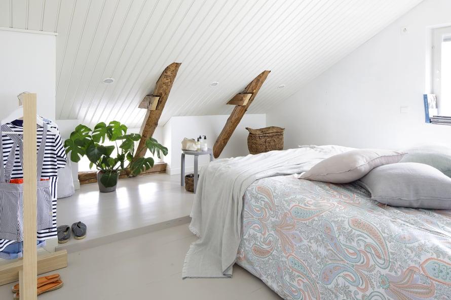 Vanhempien makuuhuone on tunnemallisen vinon katon alla. Kuva: Jaanis Kerkis
