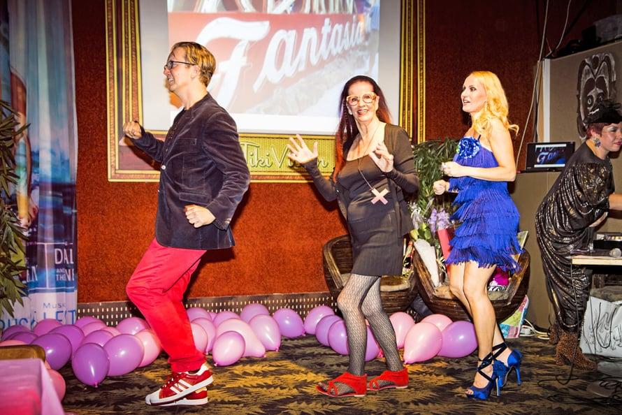"""Osku Heiskanen, Aira Samulin ja Laura Paloheimo vauhdissa kirjanjulkkareissa. Taustalla DJ ja ykkösystävä Krista Puranen Wilson """"Lady Koo"""", joka on tullut Lauran juhliin Britanniasta asti. Krista on pukeutunut teemaan sopivasti surevaksi anopiksi."""