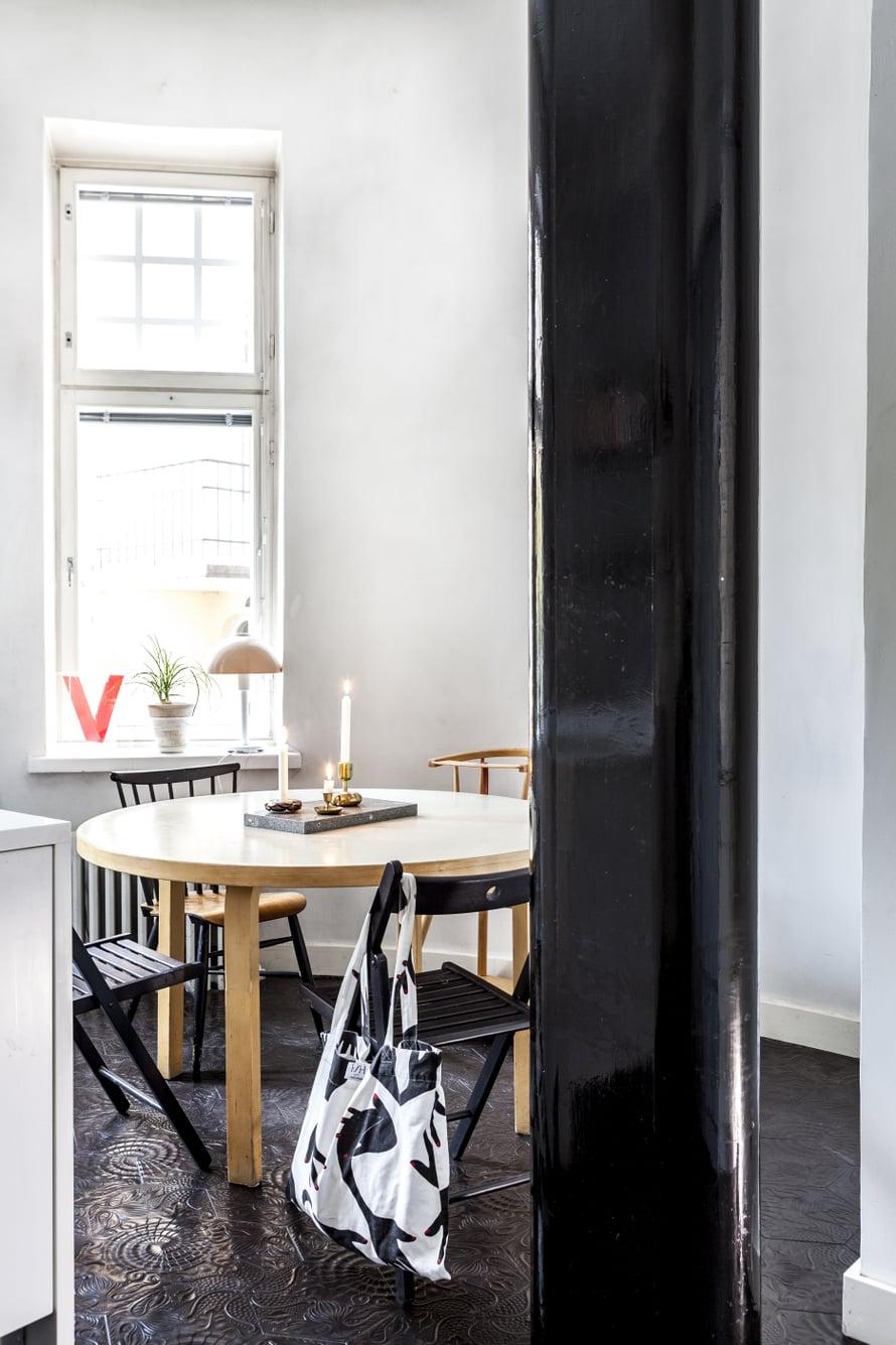 Keittiön pyöreä ruokapöytä kokoaa perheen yhteen. Kiiltävän mustaksi maalattu pylväs on keittiön katseenvangitsija.