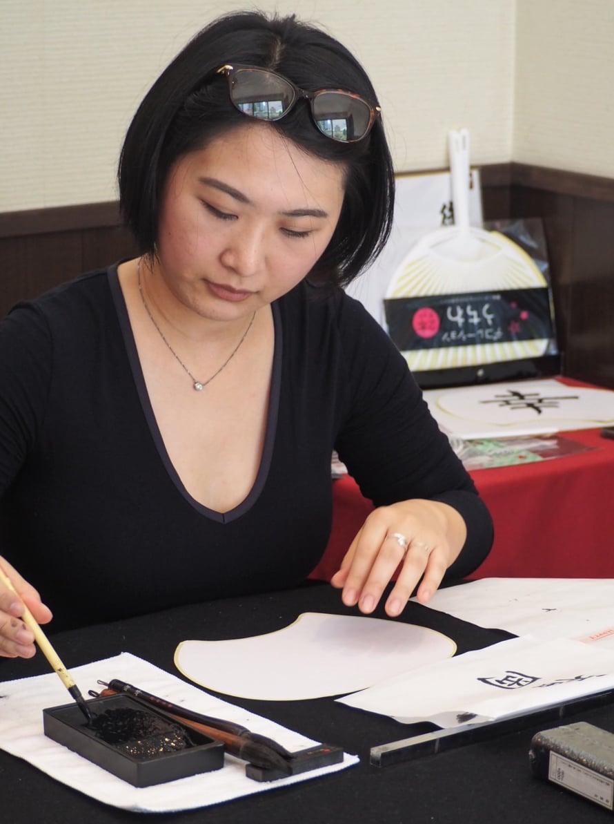 Toiselle puolelle viuhkaa kirjoitin Onnellisuus-sanan kiinalaisilla kanjimerkeillä. Toiselle puolelle Naoko kirjoittaa Fukuoka-sanan.