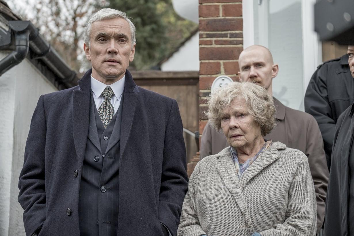 Iso-Britannian salaisen palvelun agentit kolkuttavat kirjastonhoitaja Joan Stanleyn ( Judi Dench) ovelle ja pidättävät eläkeläisnaisen syytettynä maanpetoksesta. Kuva: Finnkino