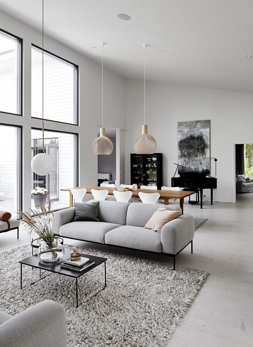 Tummat ikkunanpielet antavat ryhtiä muutoin vaaleaan tilaan. Sähköpianon takana on Virpi Mäkisen akvarelli, joka vaimentaa tilan kaikua. Bon-sohva ja sohvapöytä ovat Adean.