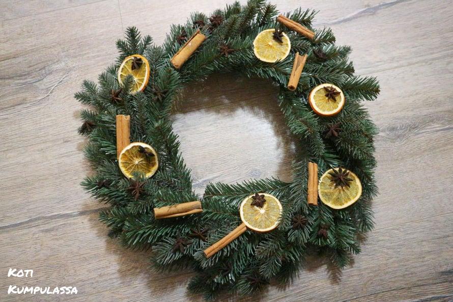 Helpon jouluaskartelun kruunasi koristeltu havukranssi, joka pääsi ulko-oveen.