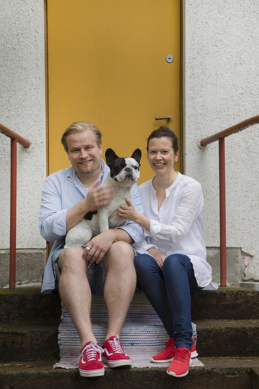 """Peppi ja Tuomo Sutisen talo on suojelukohde. Sen ikkunat ja ovet ovat alkuperäiset. Tuomon sylissä Pultti-koira. Kuva: <span class=""""photographer"""">Kaisu Jouppi</span>"""