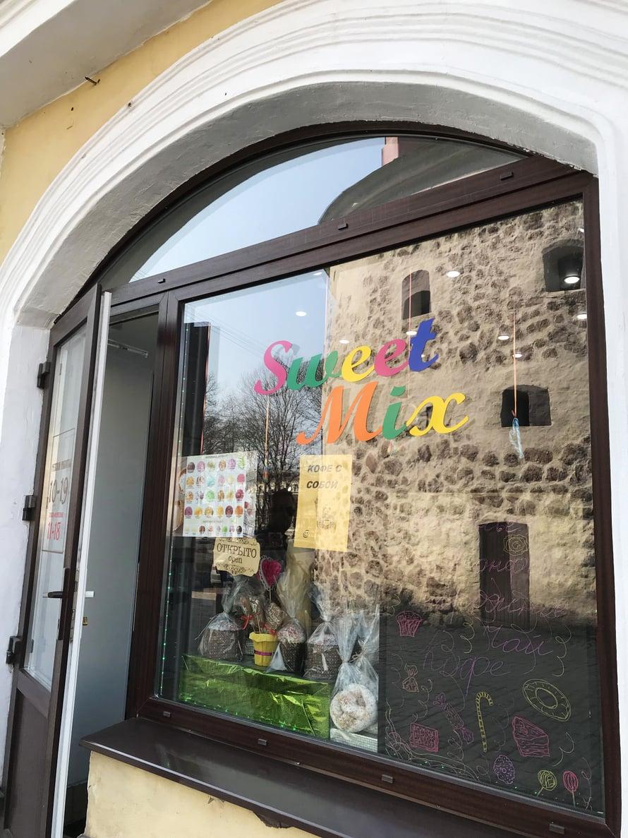 Pyöreä torni kuvastuu karkkikaupan ikkunasta. Keskiaikaisen linnanmuurin osa toimii nykyään ravintolana.