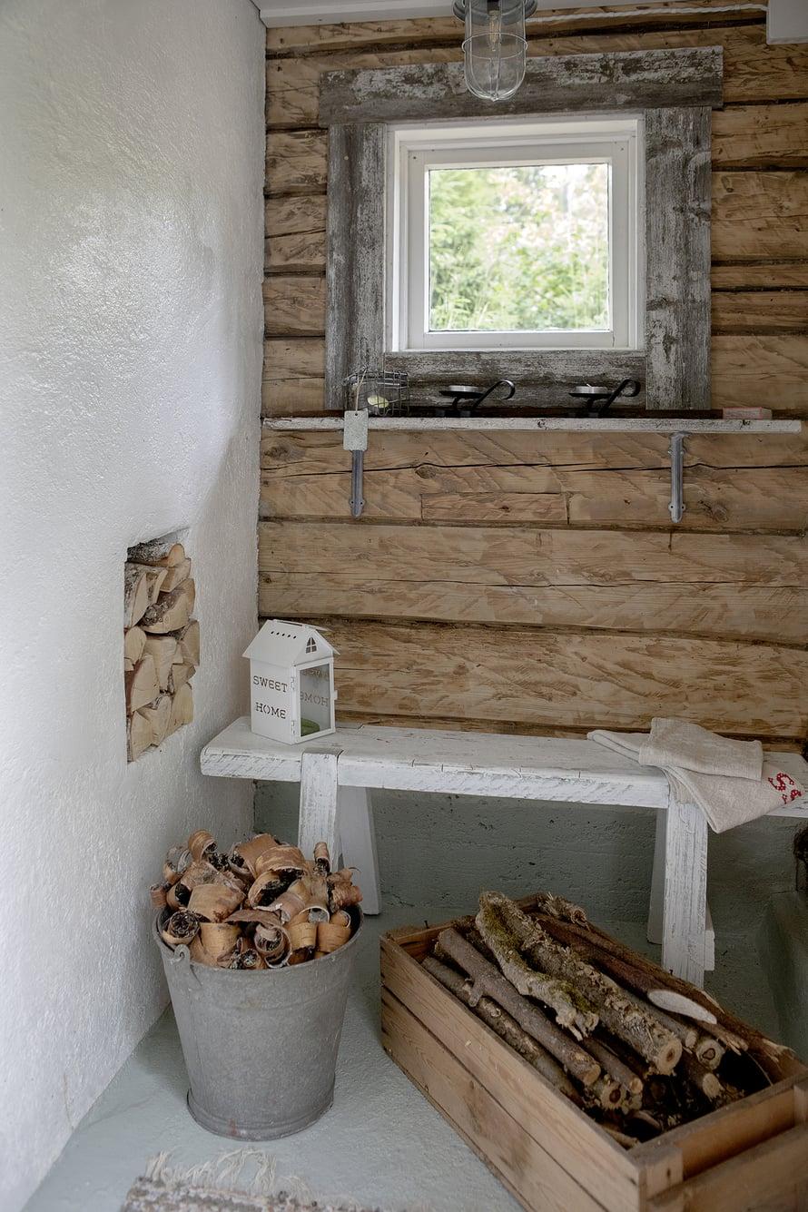 Hirsiseinä luo tunnelmaa saunaan. Pukuhuoneessa on soma pieni penkki.