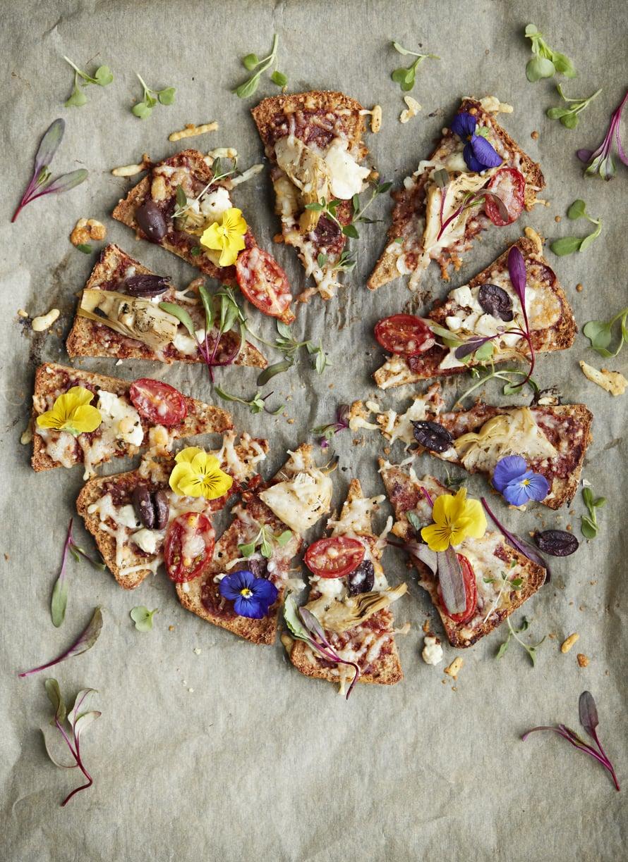 Hifistelijä koristelee lämppäripizzan syötävillä kukilla. Kaunista arkea!